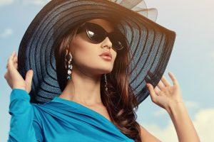 piekna kobieta w kapeluszu i okularach słonecznycz z długimi kolczykami1 300x200 - Dlaczego warto kupić kolczyki z szafirem