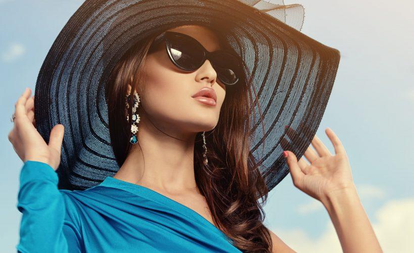 piekna kobieta w kapeluszu i okularach słonecznycz z długimi kolczykami1 820x500 - Dlaczego warto kupić kolczyki z szafirem