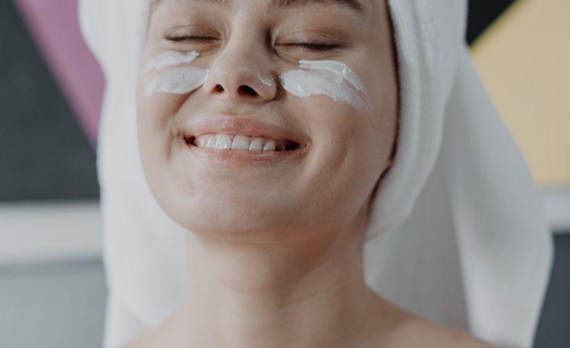 smiling woman with white towel on head 4153618 820x500 - Krem pod oczy – wybierz mądrze!