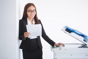 happy beautiful business woman standing copier 300x200 - Wynajem drukarek – czy warto?