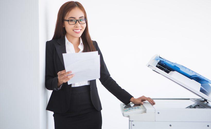 happy beautiful business woman standing copier 820x500 - Wynajem drukarek – czy warto?